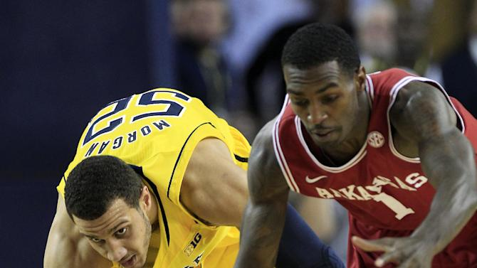 Michigan forward Jordan Morgan (52) and Arkansas guard Mardracus Wade (1) chase a loose ball during the first half of an NCAA college basketball game in Ann Arbor, Mich., Saturday, Dec. 8, 2012. (AP Photo/Carlos Osorio)