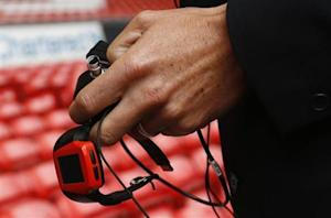Assistant Referee Probert holds a watch linked to the Hawkeye system before the English Premier League soccer match between Liverpool and Stoke City at Anfield in Liverpool