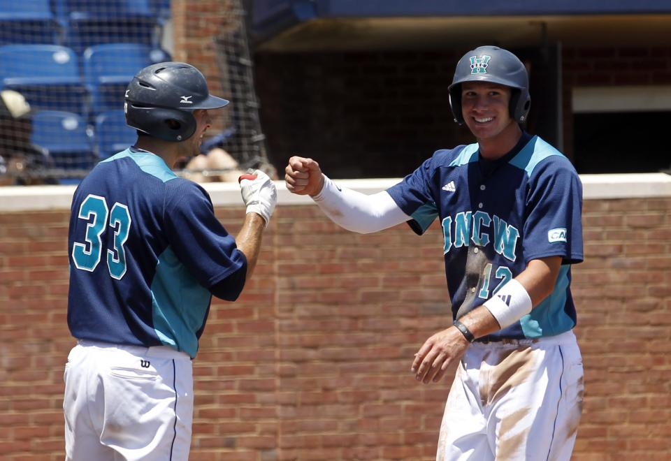 CORRECTS DATE - UNC Wilmington's Tyler Molinaro (12) celebrates scoring a run with teammate Drew Farber (33) during the first inning of an NCAA college baseball tournament regional game against Army in Charlottesville, Va., Saturday, June 1, 2013.  UNC Wilmington defeated Army 9-5. (AP Photo/Andrew Shurtleff)