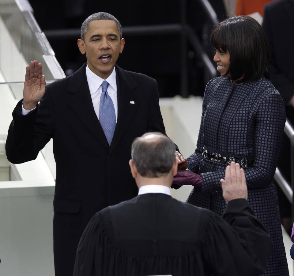 President Barack Obama receives the oath of office from Chief Justice John Roberts as first Lady Michelle holds the bible at the ceremonial swearing-in at the U.S. Capitol during the 57th Presidential Inauguration in Washington, Monday, Jan. 21, 2013. (AP Photo/Evan Vucci)