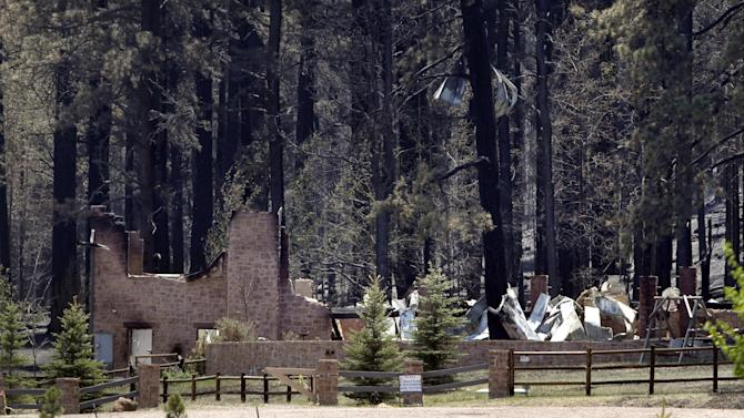 A home burned in the Wallow Fire is seen in Greer, Ariz., Monday, June 13, 2011. The focus of the battle against a massive wildfire burning in eastern Arizona shifted to New Mexico on Monday as crews lit fires around the town of Luna to stop the flames. (AP Photo/Jae C. Hong)