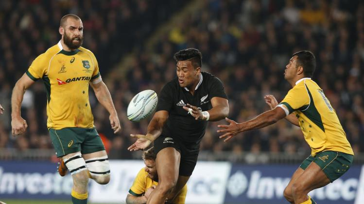 Savea of New Zealand's All Blacks gets the ball away while being tackled by McCabe of Australia's Wallabies during their second Bledisloe Cup rugby championship match at Eden Park in Auckland