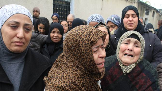 Tunisian women gather in front of the house of slain opposition leader Chokri Belaid's father prior to his funeral in Tunis, Friday, Feb. 8, 2013. Tunisia braced for clashes on Friday, with the capital shut down by a general strike and the army deployed for the funeral of a slain opposition leader expected to draw tens of thousands of mourners, and potentially many more. (AP Photo/Amine Landoulsi)