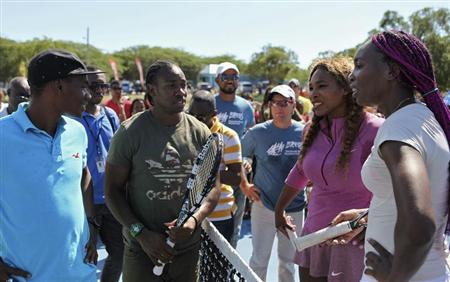 Jamaica's Olympic sprinters Warren Weir and Yohan Blake talk with Serena and Venus Williams in St. Elizabeth