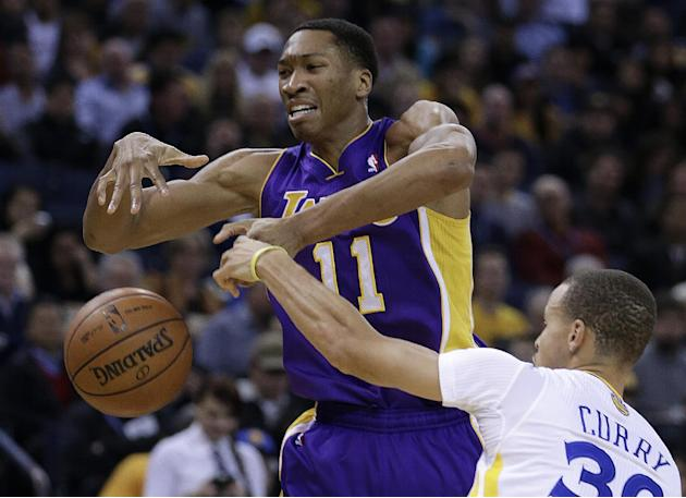 Los Angeles Lakers' Wesley Johnson, left, loses control of the ball against Golden State Warriors' Stephen Curry during the first half of an NBA basketball game Saturday, Dec. 21, 2013, in Oak