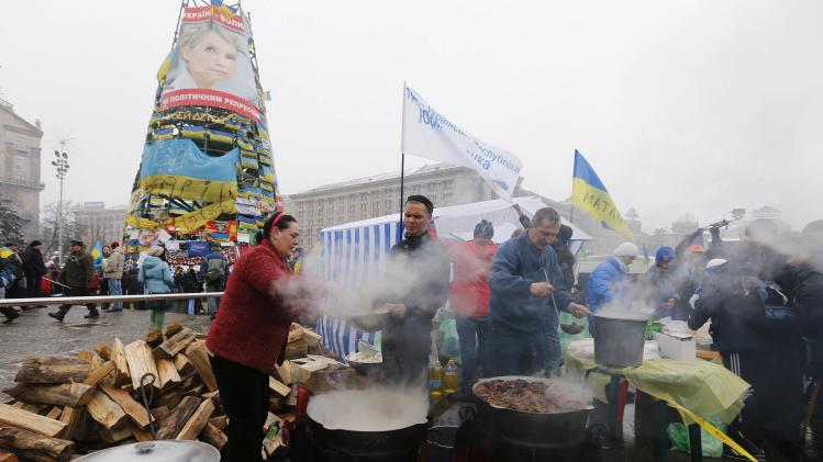 People cook in the meal area as pro-European integration protesters hold a rally in Independence Square in central Kiev