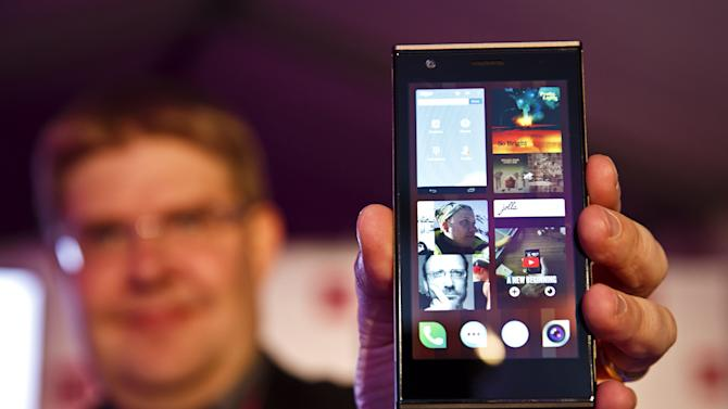 A man holds up the new Jolla smartphone from Finnish mobile manufacturer Jolla in Helsinki, Wednesday, Nov. 27, 2013. Engineers who used to work for Nokia are hoping to grab a share of the lucrative and highly competitive smartphone market with a new handset, which is based on the former world No. 1 cellphone maker's old software and is faintly reminiscent of its recent models. (AP Photo/ Lehtikuva, Roni Rekomaa) FINLAND OUT. NO THIRD PARTY SALES.