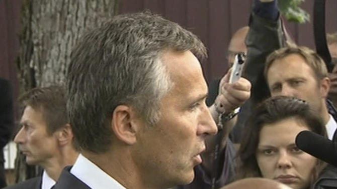 In this image from TV, Norway's Prime Minister Jens Stoltenberg, centre, talks to the media after talking with various people outside a hotel where survivors are being reunited with family members in Sundvollen, Norway, Saturday, July 23, 2011.  A Norwegian dressed as a police officer gunned down at least 84 people at an island youth retreat before being arrested, police said Saturday. Investigators are still searching the surrounding waters, where people tried to flee from the attack, which followed an explosion in nearby Oslo city centre. (AP Photo) TV OUT