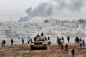Turkish soldiers on a tank and Kurdish people look…