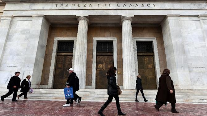 People walk in front of the Bank of Greece headquarters in central Athens on January 22, 2015
