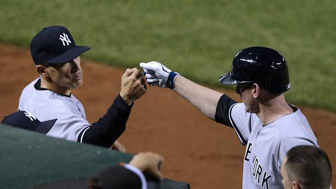 New York Yankees manager Joe Girardi, left, fist-bumps Lyle Overbay after he hit a solo home run in the seventh inning of a baseball game against the Baltimore Orioles in Baltimore, Monday, May 20, 2013. (AP Photo/Patrick Semansky)