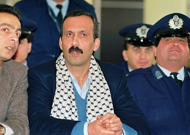 FILE - In this December 12, 1991, file photo Mohammed Rashed, center, convicted of the 1982 PanAm jetliner bombing, listens to his unidentified PLO interpreter, left, during his appeals court hearing in Athens, Greece. Rashed tucked a bomb beneath his jetliner seat cushion, set the timer and disembarked with his wife and child when the flight touched down in Tokyo. The device exploded as the jet continued on to Honolulu, killing a Japanese teenager in an attack that investigators linked to a terrorist organization known for making sophisticated bombs. It would be 20 years before Rashed, one-time apprentice to Abu Ibrahim, currently featured on the FBI list of most wanted terrorists, would admit guilt in an American courtroom. Now, credited for his cooperation against associates, Rashed is about to be freed from federal prison after more than two decades behind bars in Greece and the United States. (AP Photo/Aris Saris, File)