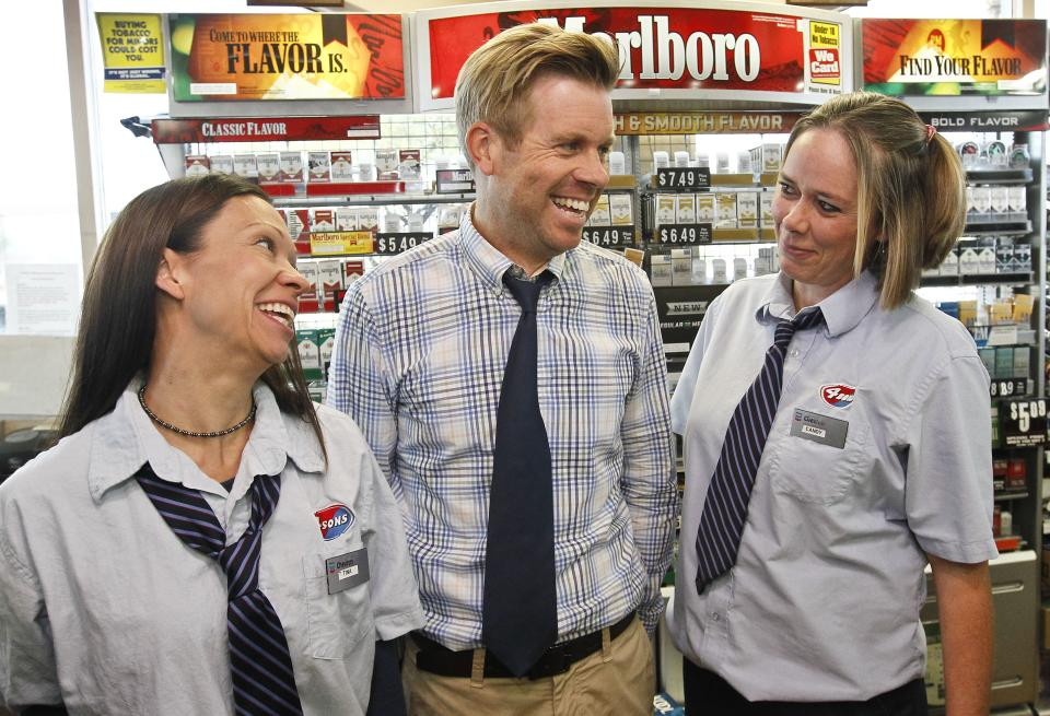 Store owner Eric Seitz, middle, laughs along with cashiers Tina Long, left, and Candy Browning at a 4 Sons Food Store where one of the winning tickets in the $579.9 million Powerball jackpot was purchased, Nov. 29, 2012, in Fountain Hills, Ariz.(AP Photo/Ross D. Franklin)