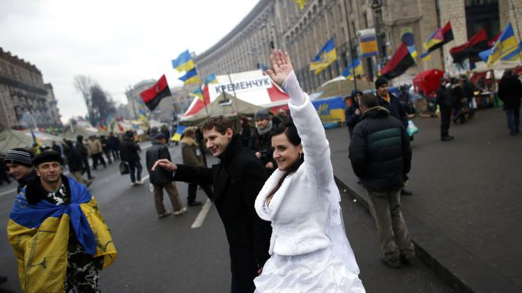A newly married couple waves to pro-EU demonstrators during a rally at Independence Square in central Kiev