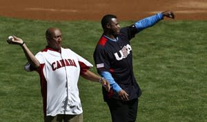 Former MLB players Ferguson Jenkins, left, of Canada, and Ken Griffey, Jr., of the United States, throw out the first pitch prior to a World Baseball Classic baseball game between Canada and the United States on Sunday, March 10, 2013, in Phoenix. THE CANADIAN PRESS/AP, Ross D. Franklin