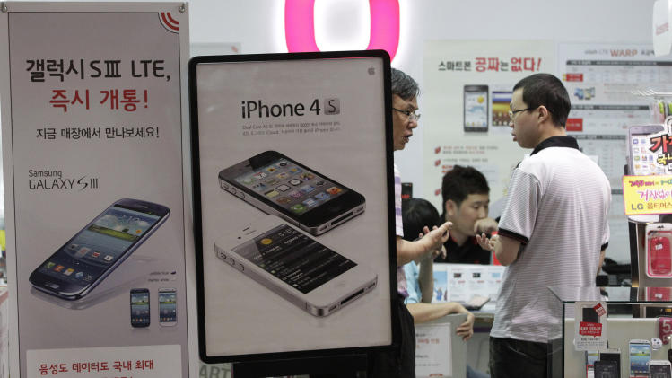 ADDITION FOR CLARIFICATION ON WHERE RULING WAS MADE - Banners advertising Samsung Electronics' Galaxy S III, left, and Apple's iPhone 4S are displayed at a mobile phone shop in Seoul, South Korea, Friday, Aug. 24, 2012. After a year of scorched-earth litigation, a jury in San Jose, Calif., decided Friday, Aug. 24, 2012 that Samsung ripped off the innovative technology used by Apple to create its revolutionary iPhone and iPad. The jury ordered Samsung to pay Apple $1.05 billion. An appeal is expected. (AP Photo/Ahn Young-joon)