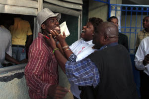 Electoral officials, right, try to calm a voter who …