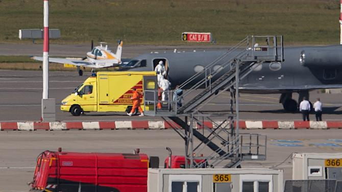 Medical staff in protective clothing transport a patient infected with the Ebola virus from a plane to an ambulance at Hamburg airport, northern Germany, on August 27, 2014