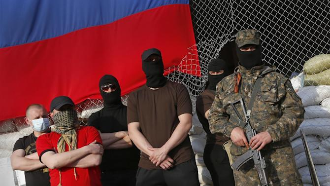 Masked pro Russian armed men stand at the city hall during negotiations about the release of foreign military observers being held by Ponomarev's group in Slovyansk, eastern Ukraine, Sunday, April 27, 2014. At least one of the eight European military observers held prisoner by pro-Russia insurgents in eastern Ukraine has been freed. Earlier in the day, the eight observers had been shown in public for the first time since they were detained on Friday and accused of spying for NATO. (AP Photo/Sergei Grits)