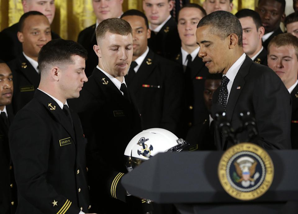 President Barack Obama is given a Navy football team helmet by players Bo Snelson, left, and Brye French, center, after presenting the Commander-in-Chief Trophy to the United States Naval Academy football team in the East Room of the White House in Washington, Friday, April 12, 2013. (AP Photo/Pablo Martinez Monsivais)
