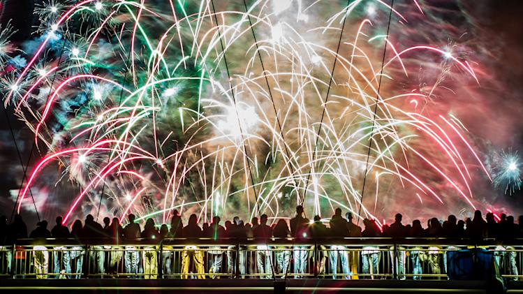 In this picture taken Sunday Aug. 31, 2014, spectators on Holbeinsteg pedestrian bridge watch the fireworks at the end of the ' festival of the museums' in Frankfurt, Germany. (AP Photo/dpa, Frank Rumpenhorst)