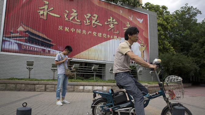 """A man smokes near a billboard with the words """"Always follow the Communist Party""""  to mark the 94 anniversary of the founding of the Communist Party of China in Beijing, China, Wednesday, July 1, 2015. (AP Photo/Ng Han Guan)"""