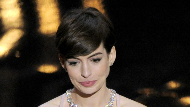 """Anne Hathaway accepts the award for best actress in a supporting role for """"Les Miserables"""" during the Oscars at the Dolby Theatre on Sunday Feb. 24, 2013, in Los Angeles.  (Photo by Chris Pizzello/Invision/AP)"""