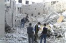 Residents stand among buildings damaged by missiles in Homs