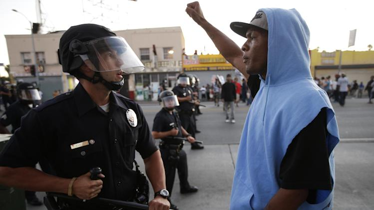 A protester confronts a Los Angles police officer during a demonstration in reaction to the acquittal of neighborhood watch volunteer George Zimmerman on Monday, July 15, 2013, in Los Angeles. Anger over the acquittal of a U.S. neighborhood watch volunteer who shot dead an unarmed black teenager continued Monday, with civil rights leaders saying mostly peaceful protests will continue this weekend with vigils in dozens of cities. (AP Photo/Jae C. Hong)