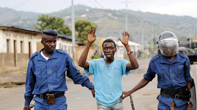 Riot policemen detain a resident participating in street protests against the ruling CNDD-FDD party's decision to allow President Pierre Nkurunziza to run for a third five-year term in office, in the capital Bujumbura