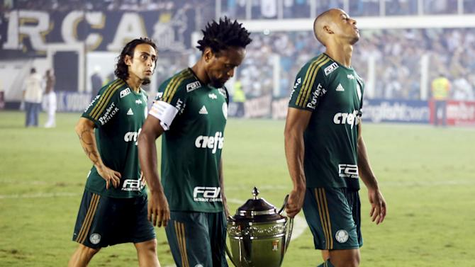Valdivia Ze Roberto and Vitor Hugo leave the field carrying the Sao Paulo state championship second place trophy after their final soccer match against Palmeiras in Santos