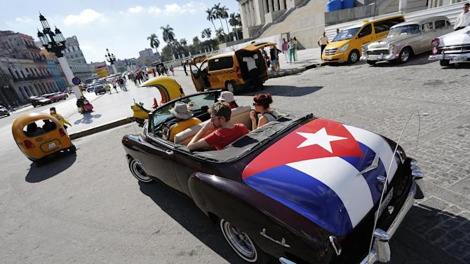 FILE - In this Dec. 18, 2014 file photo, tourists take a ride in a classic American convertible car with the Cuban national flag painted on the trunk, in Havana, Cuba. American businesses have begun imagining ways to capitalize on last week's announcement that the United States will restore diplomatic ties with Cuba and ease curbs on trade with one of the last surviving communist regimes. The opening to Cuba could benefit, among others, U.S. farmers, auto and tractor makers, airline and hotel companies and telecom equipment makers. (AP Photo/Desmond Boylan, File)