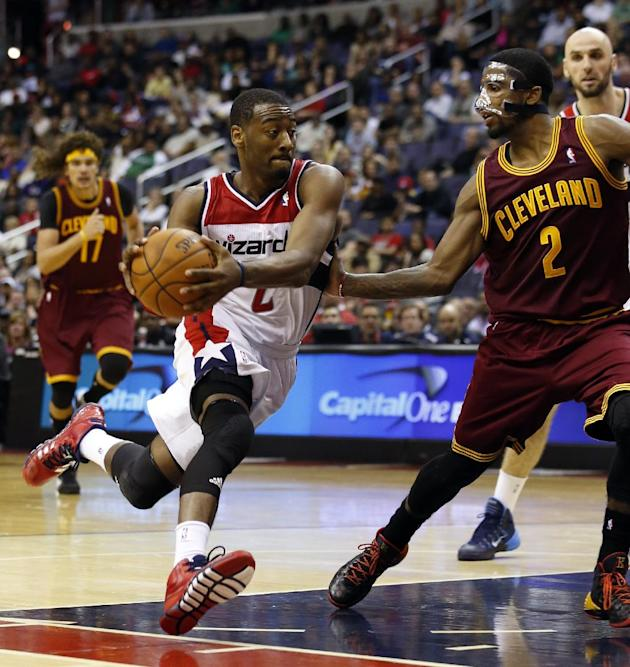 Washington Wizards guard John Wall (2) drives with the ball as he guarded by Cleveland Cavaliers guard Kyrie Irving (2) in overtime of an NBA basketball game on Saturday, Nov. 16, 2013, in Washington.
