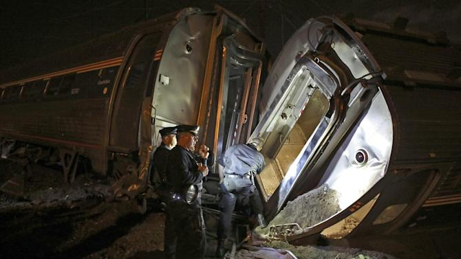 In this May 12, 2015 file photo, emergency personnel work the scene of a train wreck An Amtrak train headed to New York City derailed and crashed in Philadelphia. Amtrak says it will install video cameras inside locomotive cabs that record the actions of train engineers. The move follows a deadly derailment earlier this month in which investigators are searching for clues to the train engineer's actions just before the crash. (AP Photo/Joseph Kaczmarek, File)