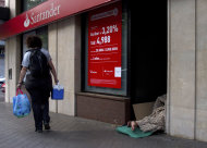 """<p>               A homeless person sleeps in the doorway of a bank in Madrid Thursday June 7, 2012. Spanish Prime Minister Mariano Rajoy pleaded with European leaders """"to support those that are in difficulty"""" and push toward greater fiscal unity - a step that might allow its troubled banks to get direct financial help. The call comes although Spain insists it doesn't need outside aid. (AP Photo/Paul White)"""