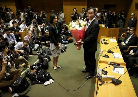Takaaki Kajita, director of the University of Tokyo's Institute for Cosmic Ray Research, receives flowers from his university during a news conference in Tokyo