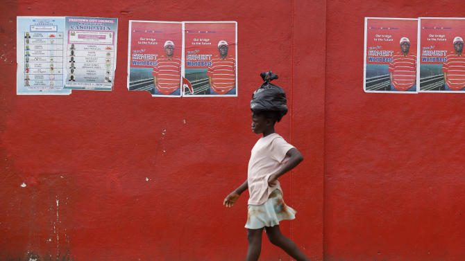 A girl walks past election posters for incumbent President Ernest Bai Koroma, in Freetown, Sierra Leone, Sunday, Nov. 18, 2012. Sierra Leoneans chose Saturday between keeping an incumbent president who has expanded health care and paved roads or electing an opposition candidate to lead this war-scarred nation still recovering a decade later despite its mineral riches. Election results were still being compiled on Sunday.(AP Photo/Rebecca Blackwell)