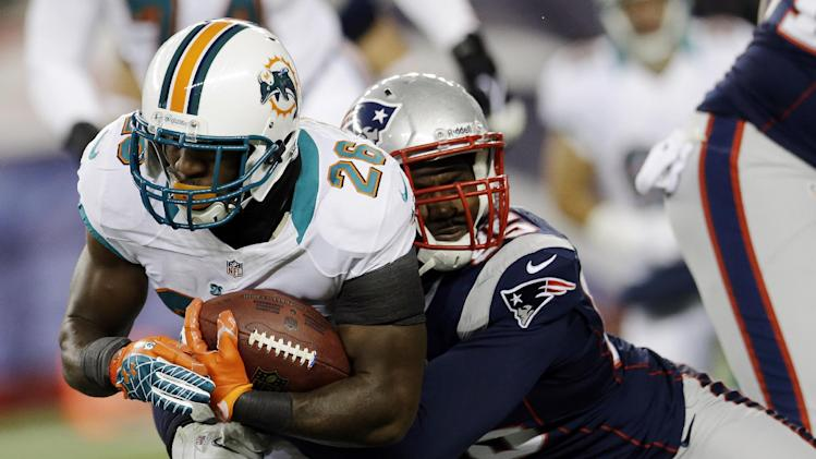 New England Patriots defensive end Chandler Jones, right, tackles Miami Dolphins running back Lamar Miller (26) during the first quarter of an NFL football game in Foxborough, Mass., Sunday, Dec. 30, 2012. (AP Photo/Elise Amendola)