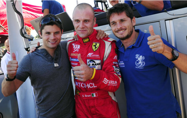 AF Corse Ferrari teammates, from left, Pierre Kaffer, of Germany, Gianmaria Bruni, of Italy, and Giancarlo Fisichella, also of Italy, celebrate Bruni's GT class pole position for the American Le Mans