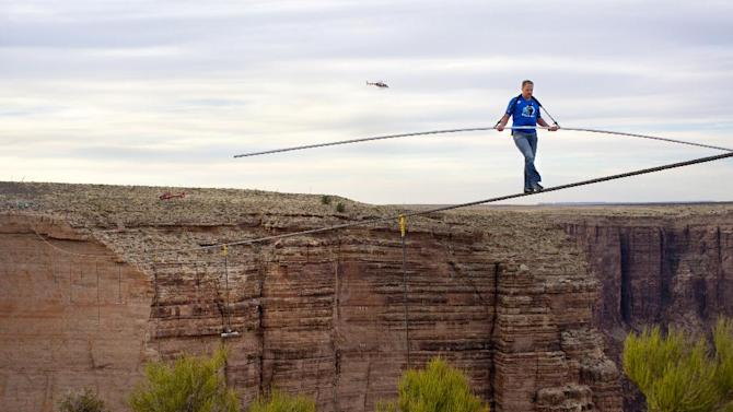 "FILE - This June 23, 2013 file photo released by Discovery shows Nik Wallenda walking across the Grand Canyon for Discovery Channel's ""Skywire Live With Nik Wallenda"" at Grand Canyon National Park in Arizona. allenda is taking his tightrope to Chicago for a high-wire walk to be televised this fall on Discovery, part of the network's strategy to entice viewers with live events. Wallenda's walk across the Grand Canyon last year reached more than 10 million viewers live on Discovery. His encore will probably take place in November, Discovery said on Thursday, April 3, 2014. (AP Photo/Discovery, Tiffany Brown, File)"
