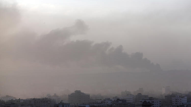 Amidst the morning fog, smoke from an Israeli strike rises in the air over Gaza City, Saturday, July 26, 2014. Israel-Hamas fighting looked headed for escalation after U.S. Secretary of State John Kerry failed Friday to broker a weeklong truce as a first step toward a broader deal. Hours after the U.S.-led efforts stalled, the two sides agreed to a 12-hour humanitarian cease-fire to begin Saturday. However, the temporary lull was unlikely to change the trajectory of the current hostilities amid ominous signs that the Gaza war is spilling over into the West Bank. (AP Photo/Lefteris Pitarakis)