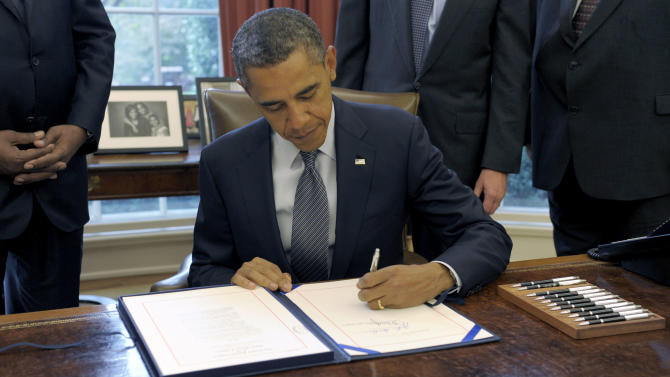 President Barack Obama signs the renewal of the Trade Adjustment Assistance for workers, Friday, Oct. 21, 2011, in the Oval Office of the White House in Washington.  (AP Photo/Susan Walsh)