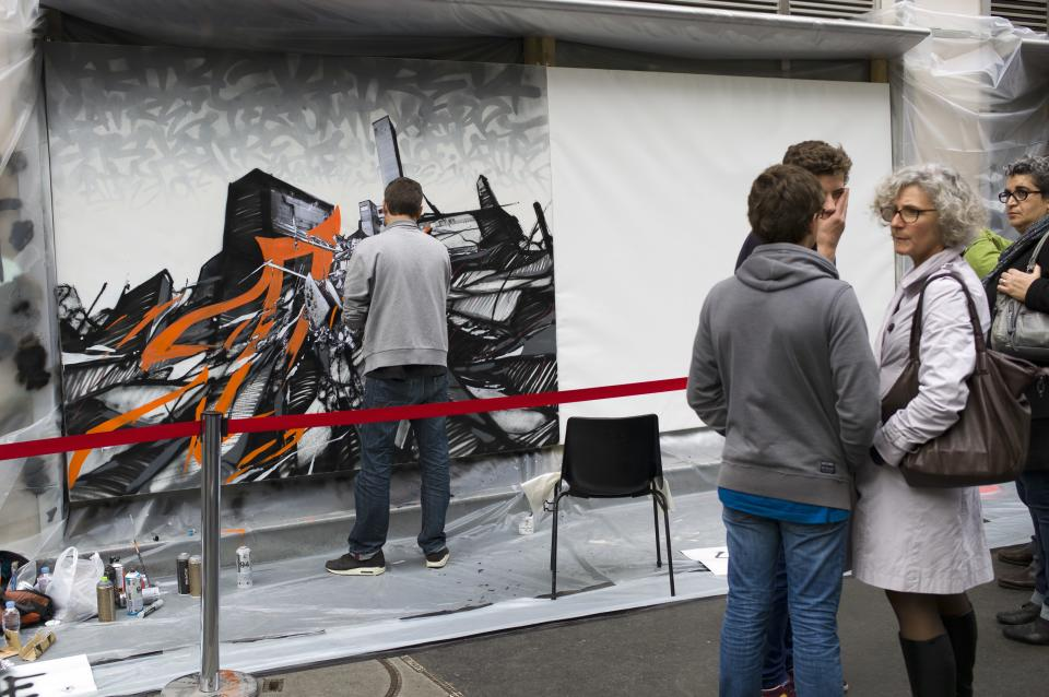 French artist Katre, left, draws a painting in the street outside Drouot auction house, in Paris, Thursday Oct. 24, 2013. This painting is one among dozens of art pieces from street artists which will be auctioned Friday Oct. 25. (AP Photo/Thibault Camus)