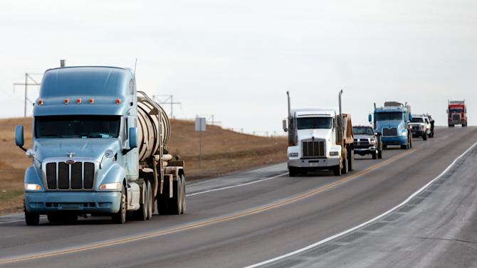 In this March 23, 2012, photo semi-trucks drive north on Highway 85 south of Williston, N.D. Touring bicyclists wanting to retrace the path of explorers Lewis and Clark or pedal through the northern tier of the U.S. are being warned to steer clear of northwest North Dakota because of heavy oil traffic. (AP Photo/Elijah Nouvelage)