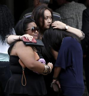 Mourners react after exiting McLaughlin Funeral Home during visitation hours for Jersey City Police Department officer Melvin Santiago, who was killed Sunday, July 13 while on duty, Thursday, July 17, 2014, in Jersey City, N.J. The officer was shot in the head while still in his police vehicle as he and his partner responded to an armed robbery call at a pharmacy. (AP Photo/Julio Cortez)