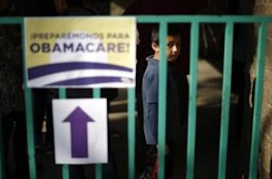 A boy waits in line at a health insurance enrollment event in Cudahy, California