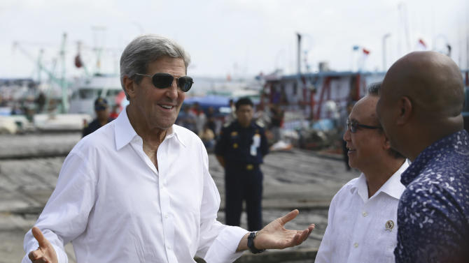 """U.S. Secretary of State John Kerry speaks to officials during a visit to a tuna packaging factory in Bali, Indonesia, Sunday, Oct. 6, 2013. Kerry said Sunday that a pair of U.S. military raids against militants in North Africa sends the message that terrorists """"can run but they can't hide."""" Kerry, in Bali for an economic summit, was the highest-level administration to speak about the operations yet. (AP Photo)"""