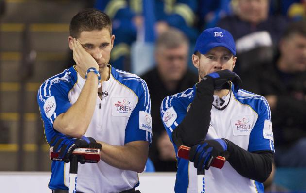 Team British Columbia skip John Morris and third Jim Cotter watch team Alberta in the 6th end during the championship draw at the 2014 Tim Hortons Brier curling championships in Kamloops