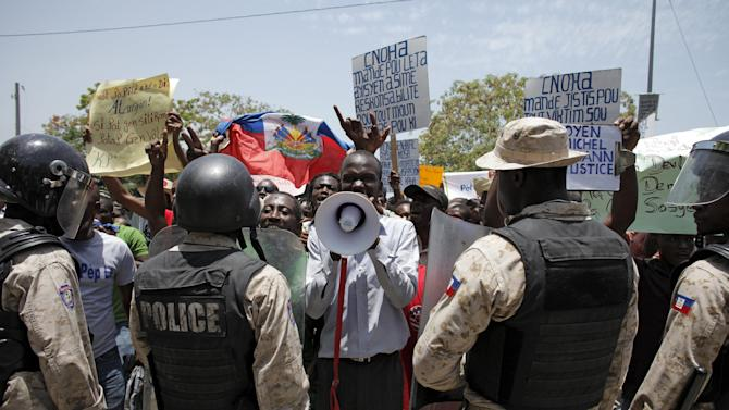 Man uses a megaphone while standing in front of policemen during a protest against the governmental corruption and the release of kidnapper Woody Etheart in Port-au-Prince