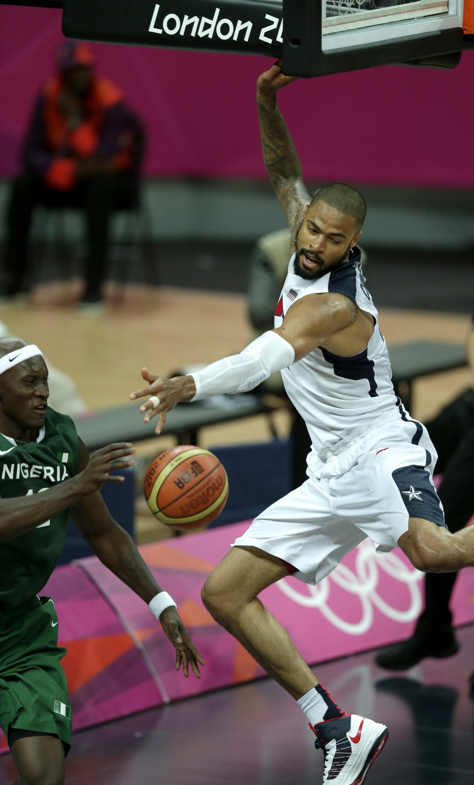 United States' Tyson Chandler, right, tries to block a pass by Nigeria's Ejike Ugboaja during a men's basketball game at the 2012 Summer Olympics, Thursday, Aug. 2, 2012, in London. (AP Photo/Charlie Riedel)